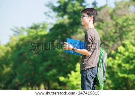 Asian student holding books and smiling while standing in park at college - stock photo