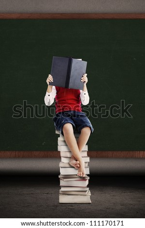 Asian student read a book on stack of books in a classroom