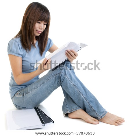 Asian student sitting on floor, reading on book. - stock photo