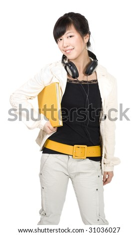 Asian student standing and smiling with yellow book and headphones - stock photo