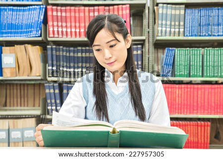 Asian student with open book reading it in college library - stock photo