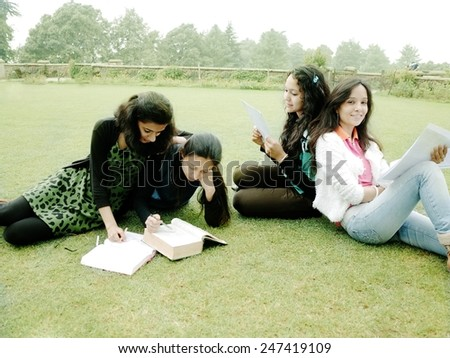 Asian students studying on grass. - stock photo