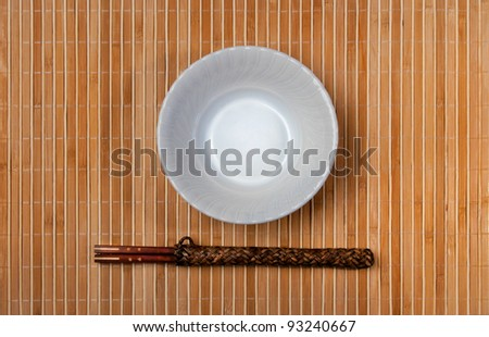 asian style bowl and chopstick on bamboo background. - stock photo