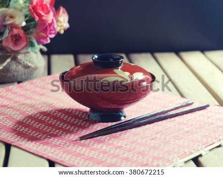 asian style bowl and chopstick on wooden table in vintage style. - stock photo