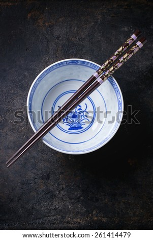 Asian style porcelan bowl and brown chopstick over black metal background. Top view - stock photo