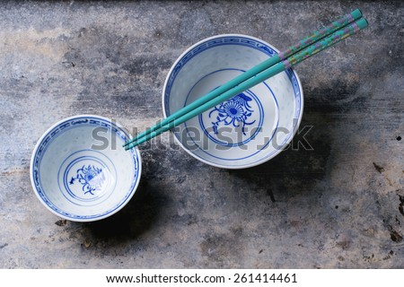 Asian style porcelan bowls and turquoise chopstick over gray metal background. Top view - stock photo