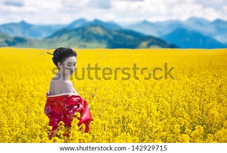 Asian style portrait of a woman with bare shoulders looking back in the yellow flowering field, mountains background - stock photo