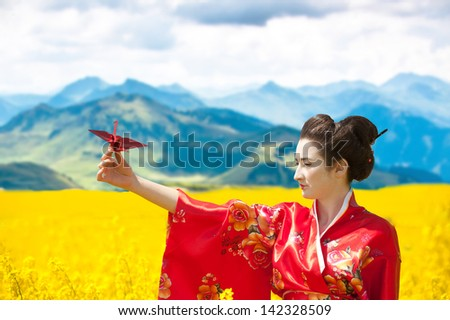 Asian style portrait of a woman with the origami crane in her hand in the yellow flowering field, cloudy sky and mountains background - stock photo