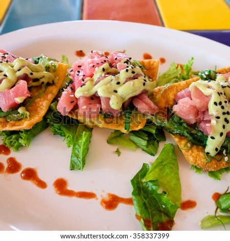 Asian style raw tuna served with seaweed on fried wonton. - stock photo