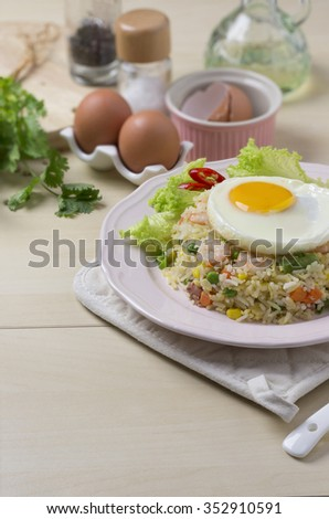Asian style seafood fried rice with sunny side up egg on wooden kitchen counter top.  - stock photo