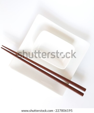 Asian table white plate and brown wood chopstick - stock photo