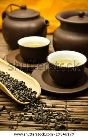 Asian tea set with dried green tea on a bamboo surface. - stock photo