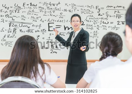 Asian teacher with a group of high school students in classroom