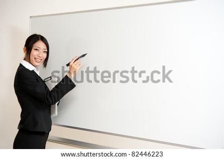 asian teacher writing to blank whiteboard - stock photo