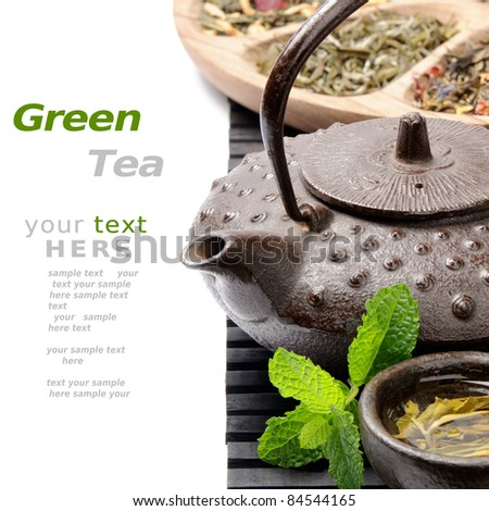 Asian teapot with green tea selection - stock photo