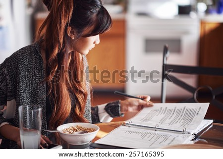 asian teen doing homework on kitchen table - stock photo