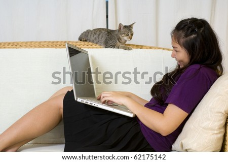 Asian teen laying on sofa with computer and pet cat