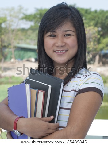 Asian teenage student holding books