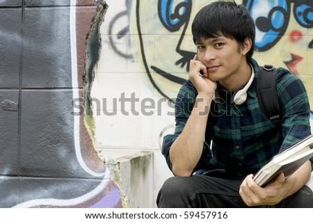 Asian teenage student holding books - stock photo