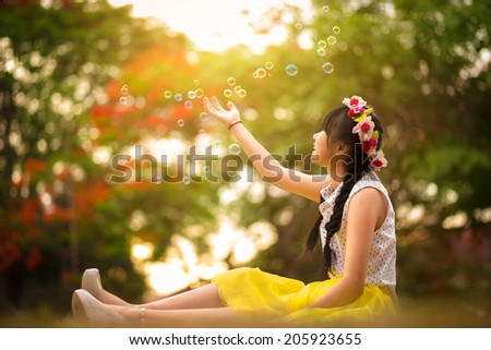 Asian teenager girl in the park under soap bubble rain - stock photo