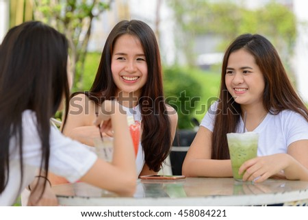 Asian teenagers friends sitting outdoors at restaurant