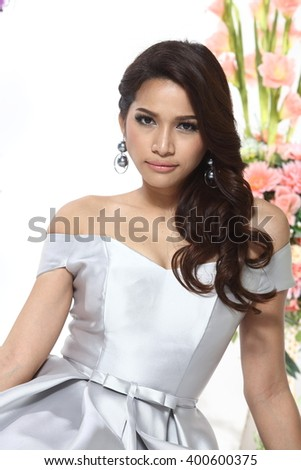 Asian Thai Female Model with Tan Skin on Fashion Make Up with Studio Lighting on White Background, silver outfit with flower