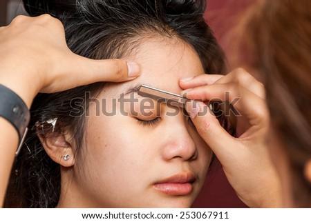 Asian Thai Girl Getting Eyebrow Shaped. - stock photo