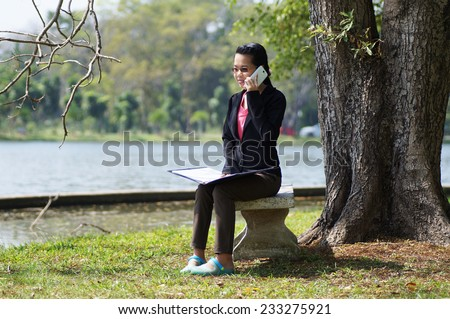 Asian, Thai girl sitting  under big tree and talking on phone