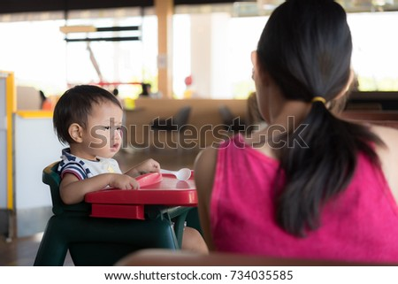 Asian toddler baby boy sitting in high chair and mother at cafe, baby in restaurant
