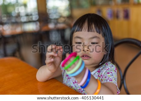 Asian toddler girl in happy time with ring toy while waiting food in a resturant