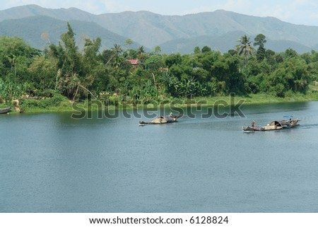 Asian traders on their small boat going to a market - stock photo