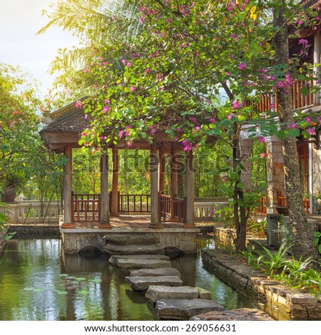 asian tropical garden with traditional bridge and buildings, Vietnam - stock photo