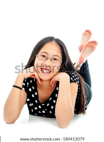 Asian tween girl lying on floor in confident pose, isolated on white background - stock photo
