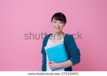 Asian university woman having laptop and textbook - stock photo