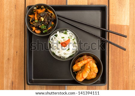 Asian vegetarian dish composed with three black bowls with shrimps, rice noodles, fried vegetables and chinese chopsticks on a square plate. Composition on a old styled wooden table. - stock photo