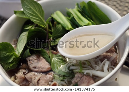 Asian, Vietnamese inspired noodle dish, Pho. Dish made with rice noodles, strips of beef, in a spicy aromatic beef broth with ginger, garlic, red chiles and topped with basil, cilantro and lime. - stock photo