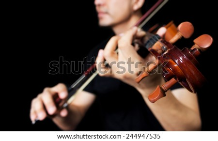 asian violinist musician plays vintage classical violin , shallow dept of field & focus to headstock / isolated on black for music background concept - stock photo