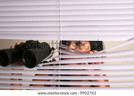 Asian woman and binoculars looking through blinds