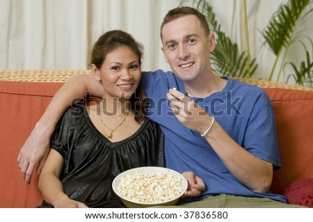 Asian woman and caucasian man eating popcorn and sitting on sofa