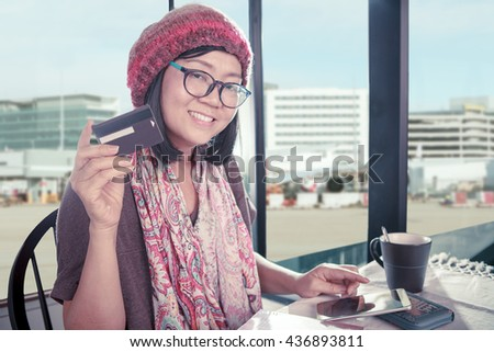 asian woman and credit card in hand sitting in urban shopping place - stock photo