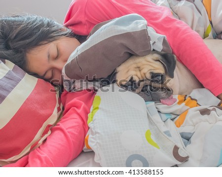 Asian Woman and her cute puppy pug dog sleep in the bed - stock photo