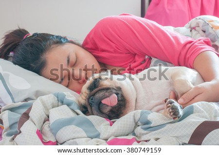 Asian Woman and her ugly pug dog sleep in the bed - stock photo