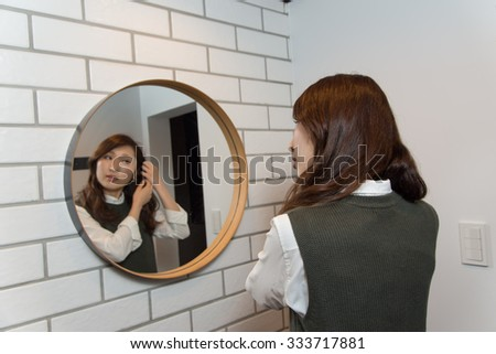 asian woman arranging her hair