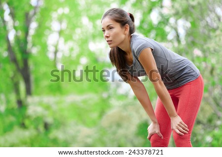 Asian woman athlete runner resting after running and jogging training outdoors in forest. Tired exhausted beautiful sports fitness model living healthy active lifestyle. Mixed race Asian Caucasian. - stock photo