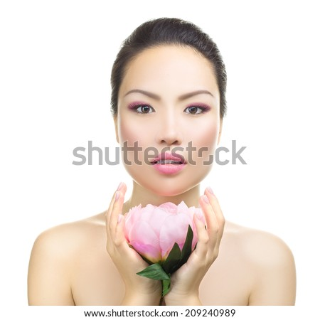 Asian woman beauty face closeup portrait. Beautiful attractive mixed race Chinese Asian / Caucasian female model with perfect skin, holding lotus flower, isolated on white background