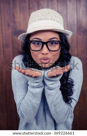 Asian woman blowing kiss to the camera against wooden wall
