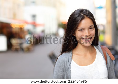 Asian woman candid portrait from street in Copenhagen city, Denmark. Young urban female smiling looking at camera. - stock photo