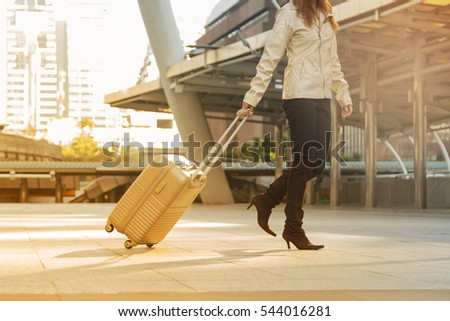 Asian woman carry suitcase travel alone in the city.