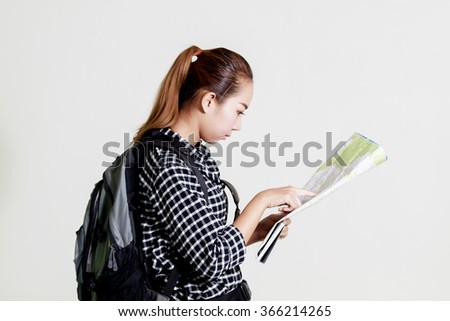 Asian woman carrying a backpack and monitoring tourist map in hand on white background