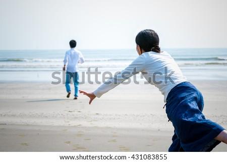 Asian woman chasing her boyfriend - stock photo